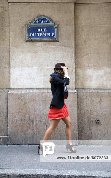 Frau  gehen  Hut  Straße  Rock  Zeichen  frontal  Bürgersteig  rot  jung  Kleidung  Inschrift  Unabhängigkeitstag  Signal