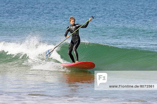stehend  einsteigen  Frau  Urlaub  Lifestyle  Sommer  Ozean  Wasserwelle  Welle  Küste  Meer  Paddel  Blaumann  Arbeitsanzug  Außenaufnahme