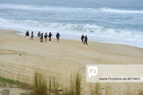 'Group of people practicing nordic walking on a beach of Mimizan (40)  in the Landes department  with the association called ''Nordicevasion''. . Nordic walking in the sand with walking poles'