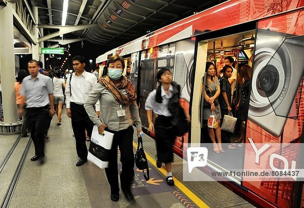 People get off the Skytrain in Bangkok