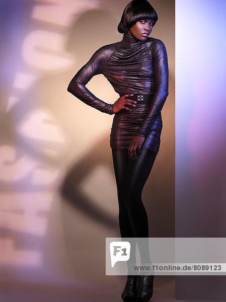 Junge Frau posiert in einem glänzenden Kleid