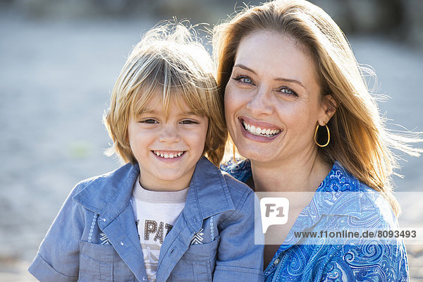 Hispanic mother and son smiling outdoors