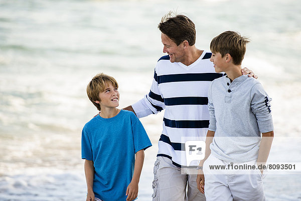 Caucasian father and sons walking on beach