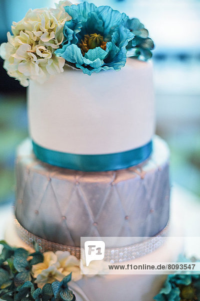Blue and silver wedding cake with flowers