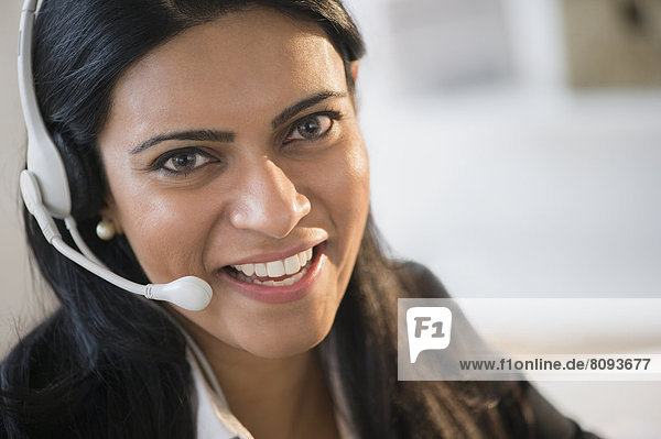 Indian businesswoman wearing headset at desk