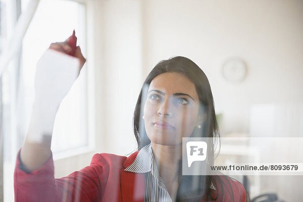 Indian businesswoman writing on glass in office