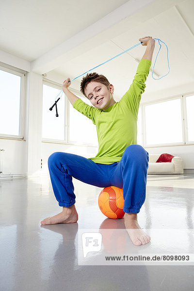 Junge in Freizeitkleidung sitzt auf Ball und hält Springseil