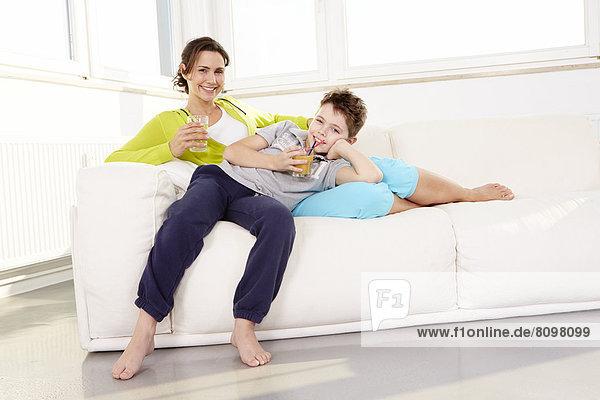 Mutter und Sohn liegen auf Sofa