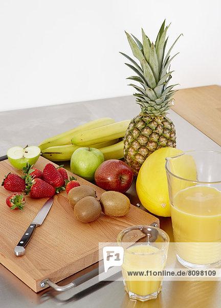 Verschiedene Sorten Obst auf Schneidebrett  daneben Orangensaft