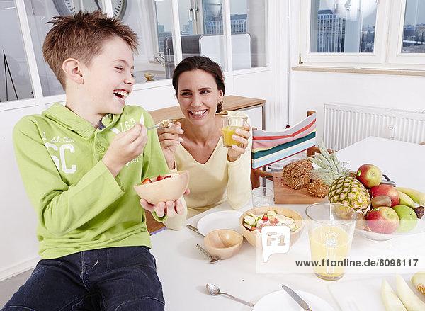 Mutter und Sohn essen frisches Obst und Müsli