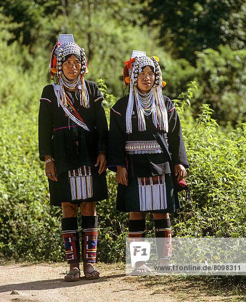 Akha-Frauen in einem Bergdorf mit traditioneller Kleidung und Kopfbedeckung  ´