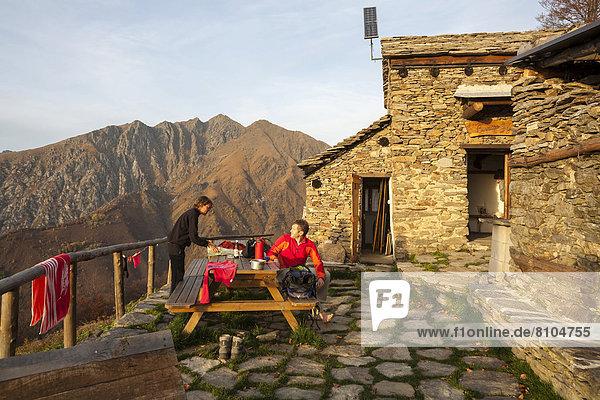 Zwei Wanderer an der Berghütte Bivacco Alpe Curgei