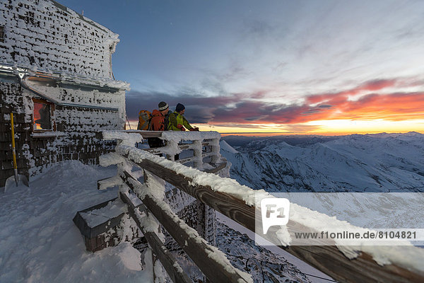 Zwei Bergsteiger beobachten den Sonnenaufgang an der Erzherzog-Johann-Hütte auf dem Großglockner