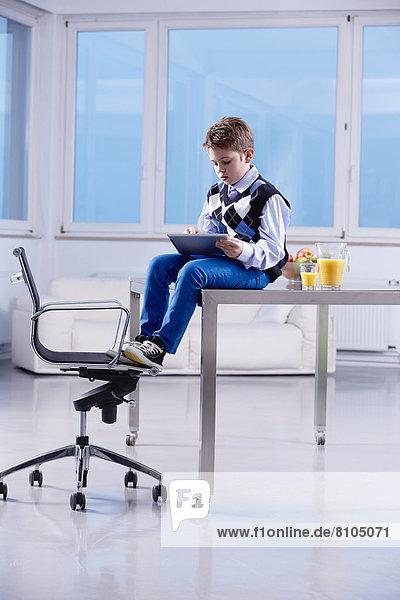 Junge sitzt mit einem Tablet-PC auf einem Schreibtisch