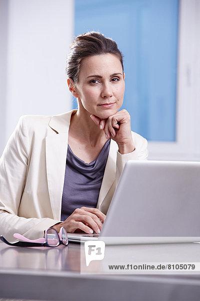 Frau sitzt mit Laptop an Schreibtisch