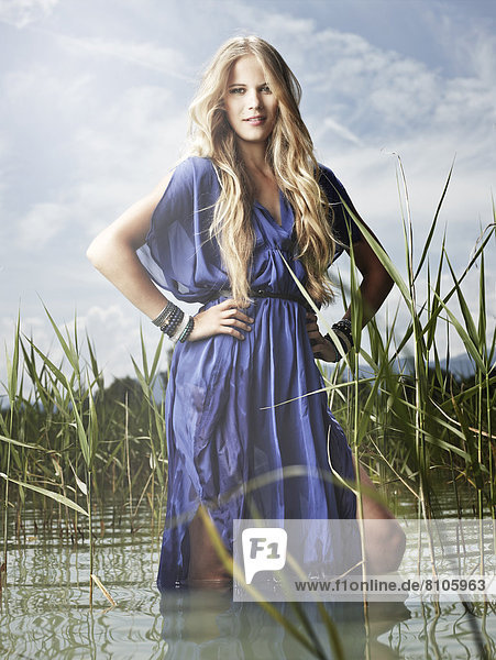 Woman wearing a blue dress standing between the reeds  fashion