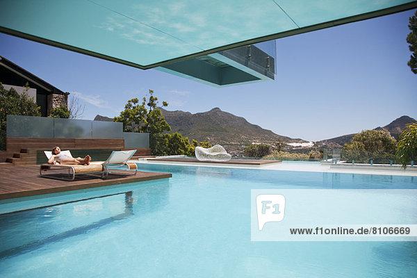 Frau beim Sonnenbaden auf Liegestuhl am Pool mit Bergblick
