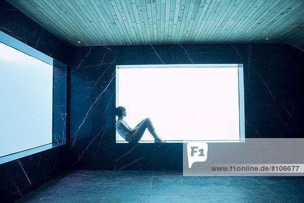 Frau sitzt auf dem Sims am Fenster im Poolraum
