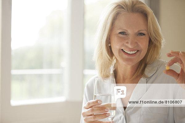 Porträt einer lächelnden Frau mit Pille und Wasserglas