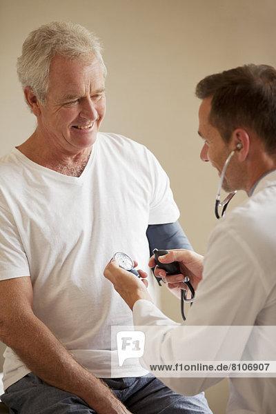 Arzt  der den Blutdruck des älteren Mannes im Büro des Arztes überprüft.