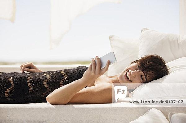Lächelnde Frau SMS mit Handy auf dem Terrassensofa