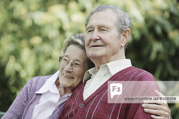Deutschland  Köln  Seniorenpaar im Park sitzend  lächelnd