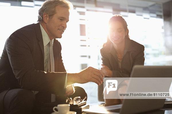 Geschäftsmann und Geschäftsfrau mit Laptop in der Lobby