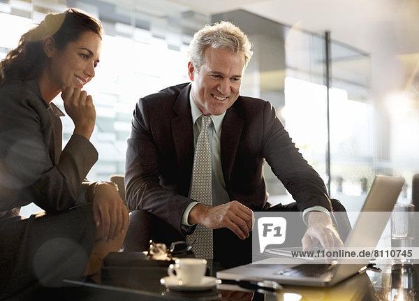 Lächelnder Geschäftsmann und Geschäftsfrau mit Laptop in der Lobby