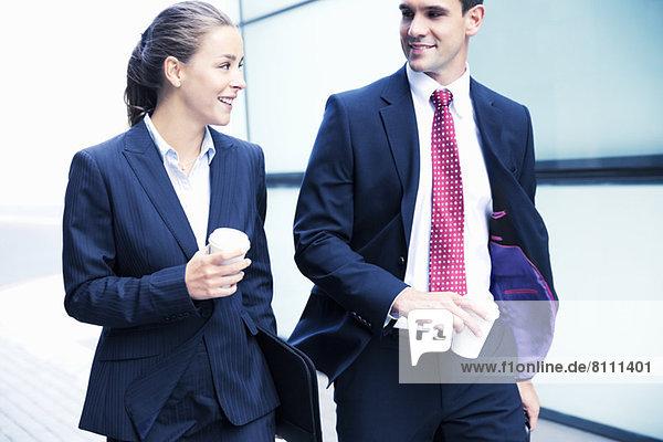 Lächelnder Geschäftsmann und Geschäftsfrau beim Kaffeetrinken