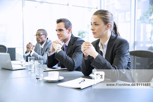 Aufmerksame Geschäftsleute mit umklammerten Händen in der Besprechung