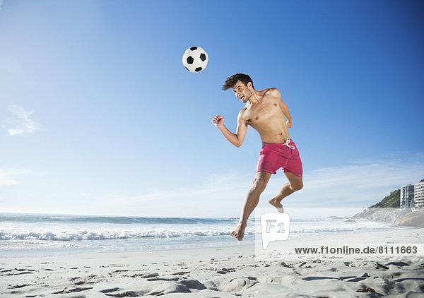 Mann in Badehose auf dem Weg zum Fußball am Strand