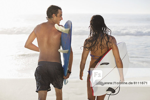 Paar Wanderungen mit Surfbrettern am Strand