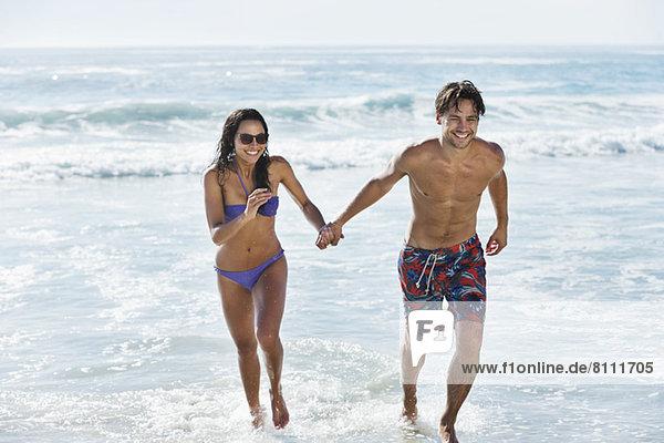 Paar läuft in der Meeresbrandung