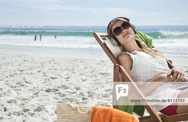 Gelassene Frau hört Kopfhörer im Liegestuhl am Strand