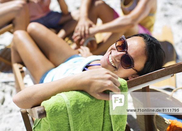 Porträt einer glücklichen Frau im Liegestuhl am Strand