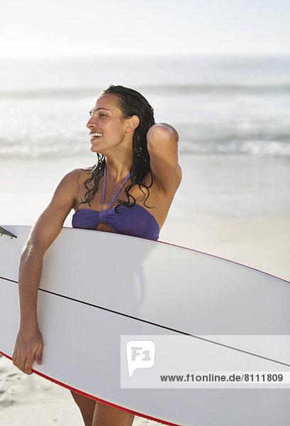 Lächelnde Frau mit Surfbrett am Strand