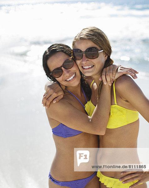 Porträt von lächelnden Frauen in Bikinis beim Umarmen am Strand
