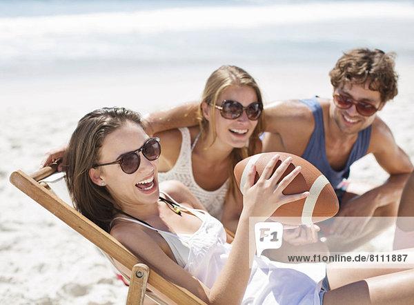 Lächelnde Freunde mit Fußball am Strand