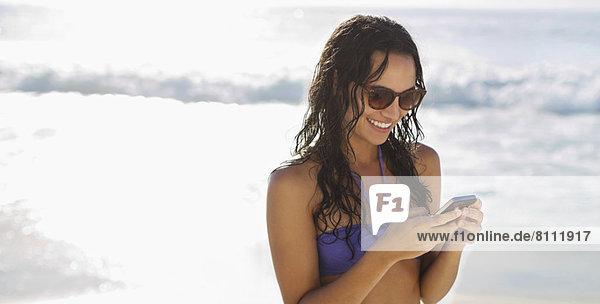 Lächelnde Frau SMS mit Handy am Strand