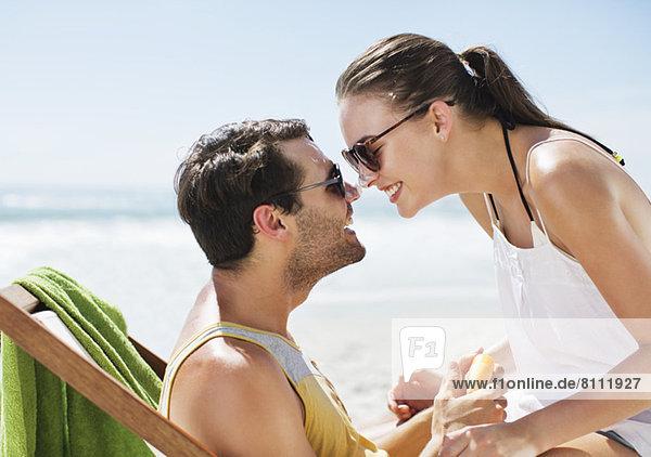 Ein glückliches Paar  das am Strand mit Sonnencreme bedeckte Nasen reibt.