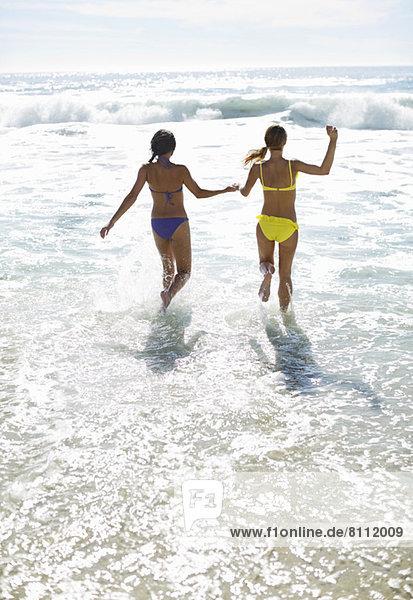 Freunde in Bikinis halten sich an den Händen und laufen ins Meer.