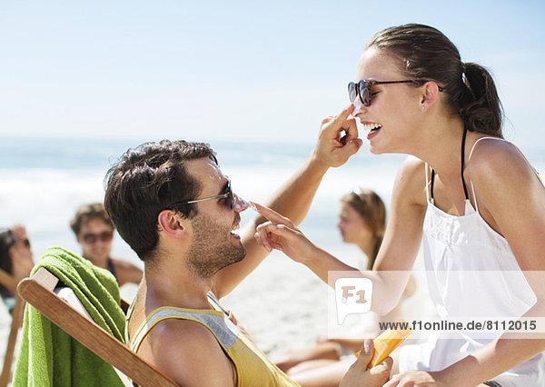 Paar  das sich gegenseitig die Nase am Strand mit Sonnencreme eincremt.