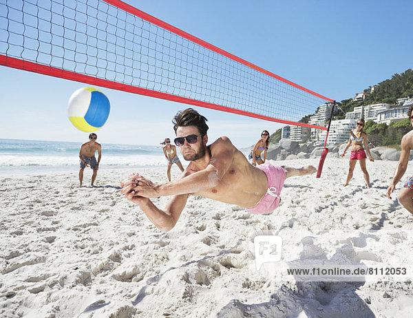 Mann taucht für Volleyball am Strand