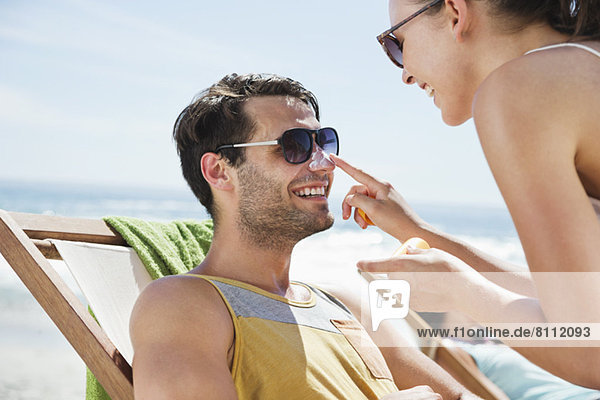 Frau  die Sonnencreme auf die Nase des Mannes am Strand aufträgt.