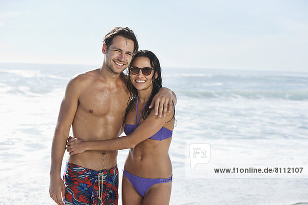 Ein glückliches Paar umarmt sich am Strand.