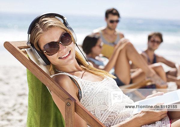 Porträt einer glücklichen Frau  die am Strand Kopfhörer hört.