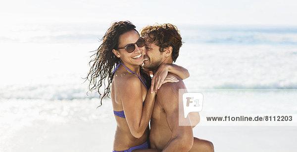 Enthusiastisches Paar  das sich am Strand umarmt
