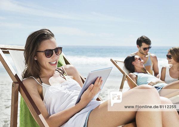 Glückliche Frau mit digitalem Tablett im Liegestuhl am Strand