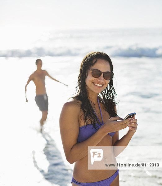 Porträt der lächelnden Frau im Bikini mit Handy am Strand