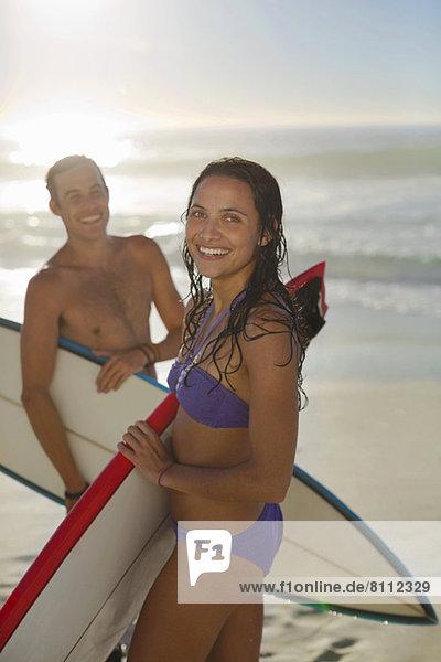 Portrait eines glücklichen Paares mit Surfbrettern am Strand
